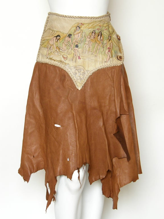 Rock chic, handmade leather wrap skirt with an irregular hem and a peaked yoke. The yoke is hand painted with images of Native Americans in a western landscape, and it has laced edges. It closes on the side with 3 buttons made from slices of natural