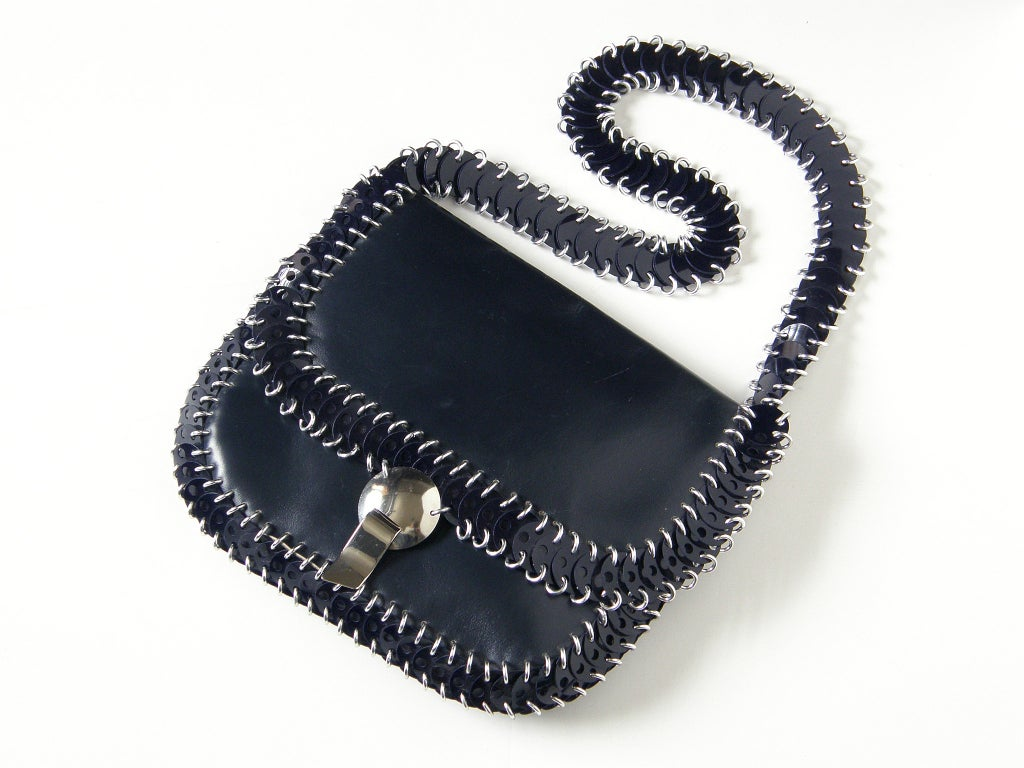 """Paco Rabanne shoulder bag in navy blue leather and plastic disks. The disks are attached with aluminum links, and the bag has a dome shaped chrome clasp with a tab and slot closure. The bag measures 19.5"""" high to the top of the strap."""