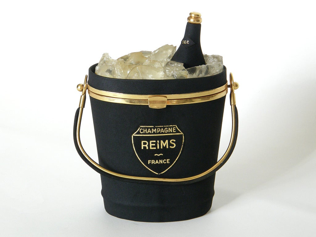 Wonderful handbag by Anne-Marie in the shape of a  champagne bucket with ice and champagne bottle. The bag is covered in black suede with gold-plated brass hardware and bottle top. The realistic ice is made of rough cut chunks of lucite. The bucket