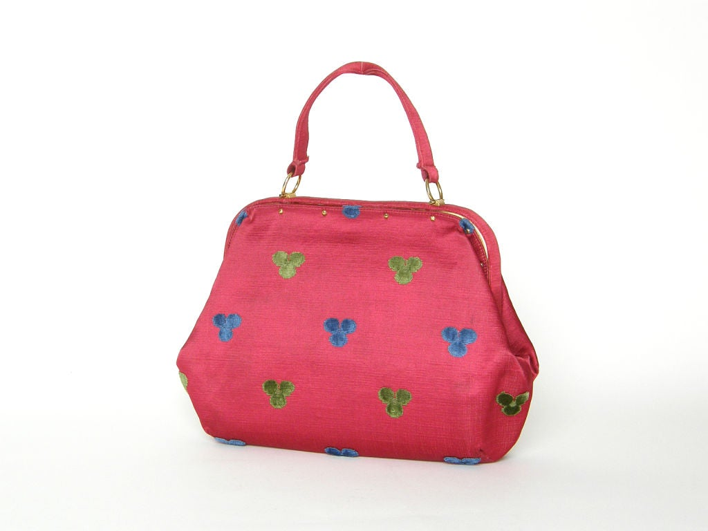 This Roberta di Camerino handbag is covered in a fuchsia silk with a raised pattern of trefoil designs in blue and green. There are decorative, gold-plated screw heads that attach the fabric cover to the metal frame. The clasp is very clever. The