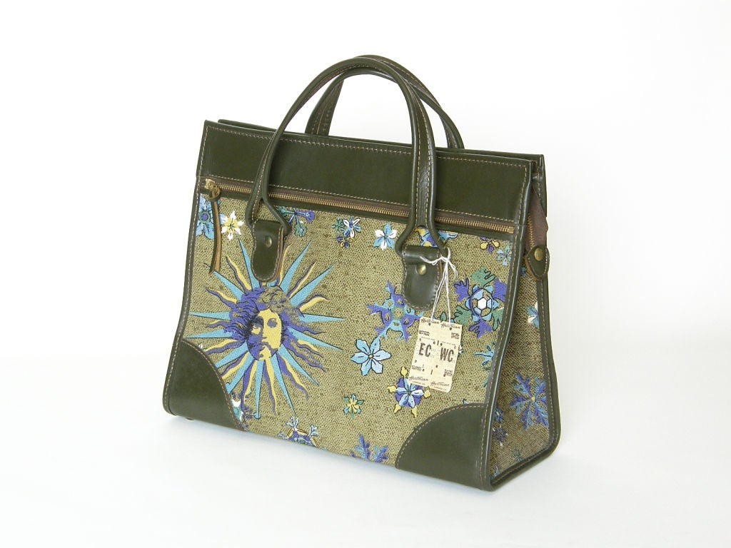 """This fashionable tote bag is from Hartmann's """"Sun God"""" line from 1969. The body of the bag is covered in fabric printed with a sun face and flowers in shades of green with light blue, purple and pale avocado accents. The handles and trim"""