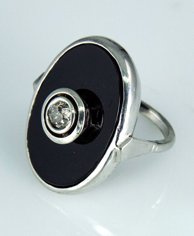 Beautiful classical elegance; designed and hand crafted in14k White Gold; this Runway Ring hallmarks the characteristics of the famed Art Deco period, the central tablet of black Onyx showcases a sparkling exquisite double bezel-set with an old