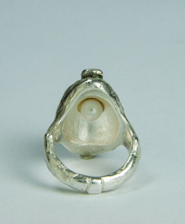 Wonderful and Whimsical Walter Schluep Figural Sterling Silver Pelican Ring; underside of ring houses a pearl; top of ring measures approx. 25.5mm x 17mm; approx. ring size 7; all handmade and hand hammered. Marked: STERLING SCHLUEP plus his