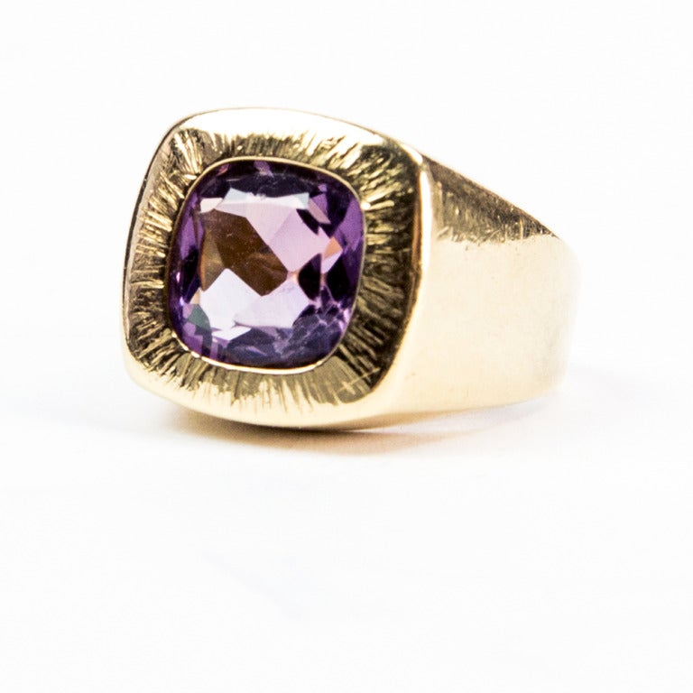 A Striking Amethyst Ring, centering a faceted cushion-cut Amethyst, bezel-set in 18k yellow gold handmade mounting; medium purplish blue; approx. Size 4.5 A Show Stopper that's Chic, Classic and Timeless!