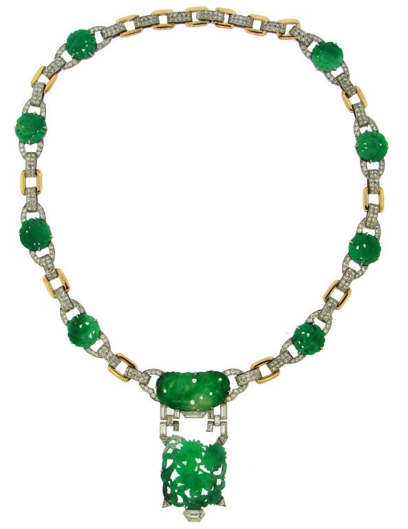 Elegant Art Deco necklace created by J.E. Caldwell & Co. in the 1920's. It features finest detailed carving on green jade medallions accentuated with baguette and single cut diamonds. Setting is made of platinum and yellow gold. The center part