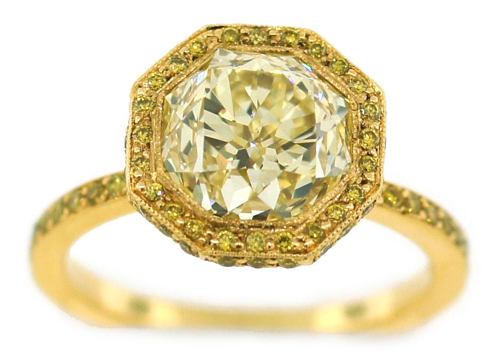 Fabulous engagement ring featuring a 3.10 carats light fancy yellow diamond set in yellow gold. The diamond is Old European cut. The setting is micropave set with round fancy vivid yellow diamonds.<br />