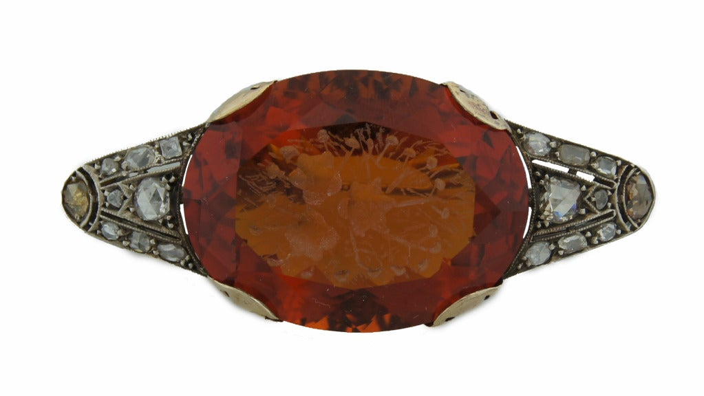 Amazing Victorian brooch created in the 1900's. Features a gorgeous 65-carat carved oval citrine accented with rose cut diamonds set in silver and yellow gold. Beautiful carving with floral motif.