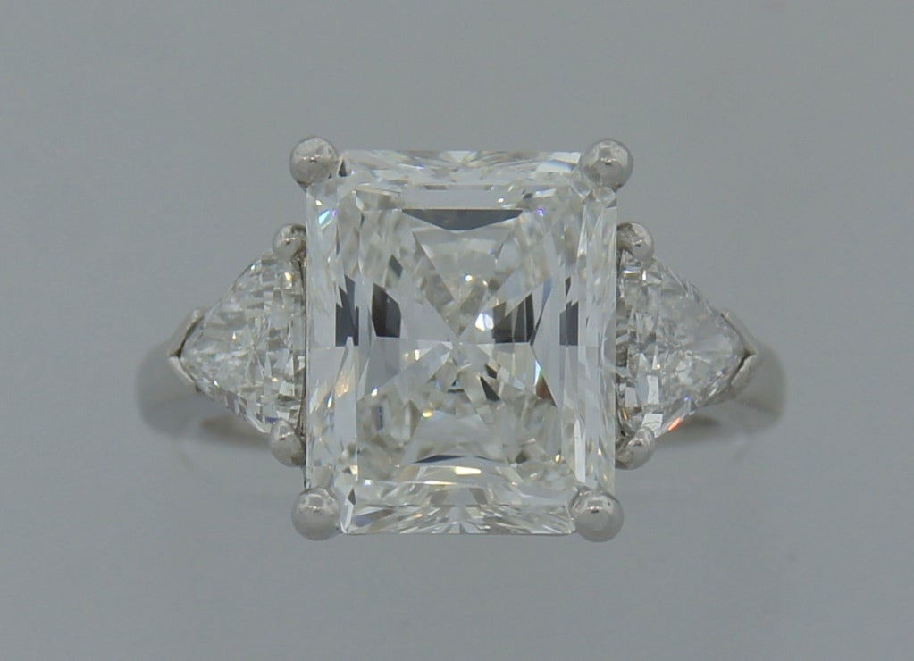 Magnificent three-stone engagement / anniversary ring created by Cartier, New York. Features a 4.83-ct rectangular brilliant cut diamond (F color, VS1 clarity evaluated by GIA and coming with a GIA Diamond Grading Report dated January 11, 2012). The