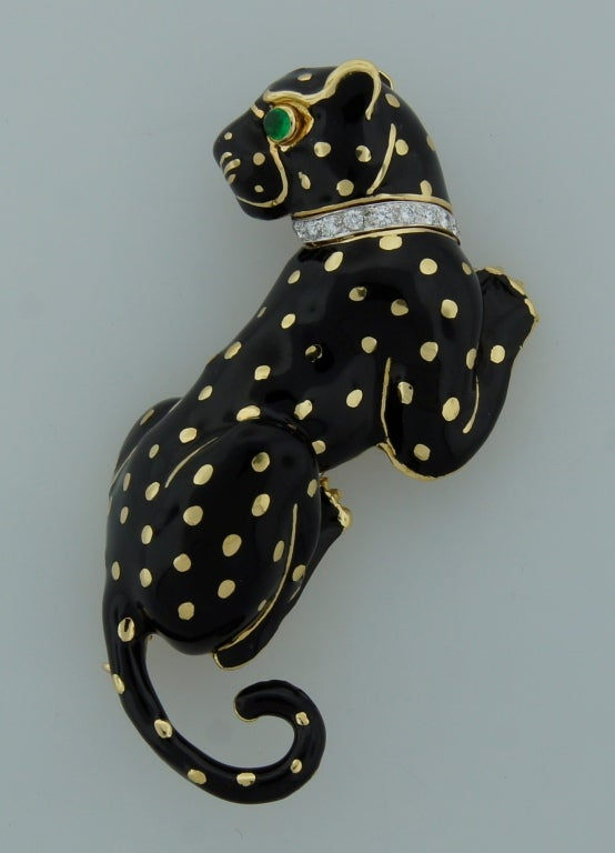 Bold and chic panther pin created by David Webb in the 1970's.  Gracious panther posture, outstanding workmanship on enamel, tasteful diamond collar and accented with an emerald panther's eye - are the highlights of this fabulous piece. The
