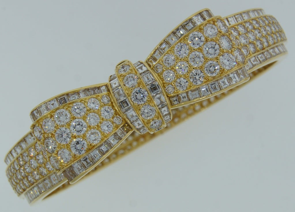 Exquisite and feminine bracelet created by Van Cleef & Arpels in Paris in the 1970's. It is made of yellow gold in the shape of an elegant bow and encrusted all over with round brilliant diamonds. Diamond total weight approximately 10 carats (E-F