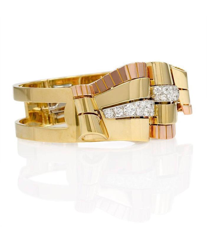 A Retro gold and diamond bracelet with a pair of scrolling two-color gold removable dress clips on an open gold frame, in 18k and platinum. Van Cleef & Arpels, France. #47901. Brown suede box from VCA.  Atw diamonds 2.50 cts.