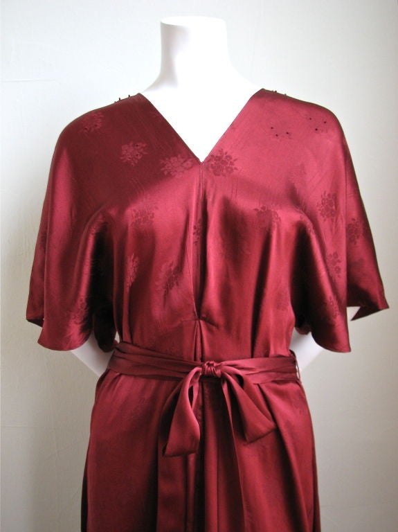 Gorgeous French silk brocade dress dating to the 1930's. Wonderful rich burgundy shade. Light embroidery at neckline. Extra long waist ties. Slips on over the head. French seams throughout. This is an impeccably made dress. Excellent condition. Best