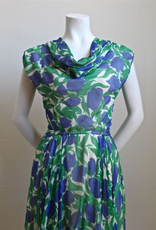 "Beautiful vibrant floral silk chiffon dress from Bonwit Teller dating to the 1950's. Fits a size 6 or 8. Bust measures approximately 35"", waist is 26"" and dress is 42"" long. Fully lined. Zips and snaps up back. Very good condition."