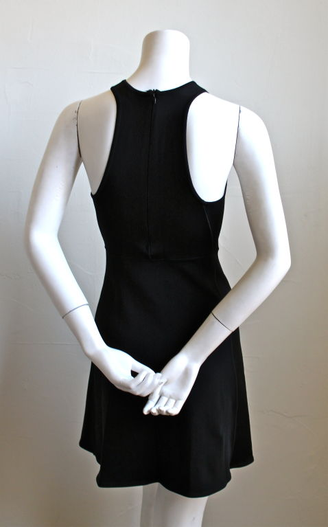 Streamlined jet black mini-dress with racer back from Azzedine Alaia dating to the 1990's. Labeled a size S. Zips up center back. Made in Italy. Excellent condition.