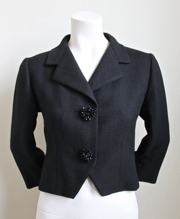 Jet black haute couture wool jacket with decorative buttons from Balenciaga dating to the 1960's. Fits a size 4-6. Fully lined. Made in France. Excellent condition.