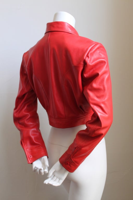 Vibrant red cropped leather jacket with sweetheart seamed construction from Azzedine Alaia dating to the 1980's. Best fits a size 4 or 6. Made in France. Very good condition with light fading to the color.