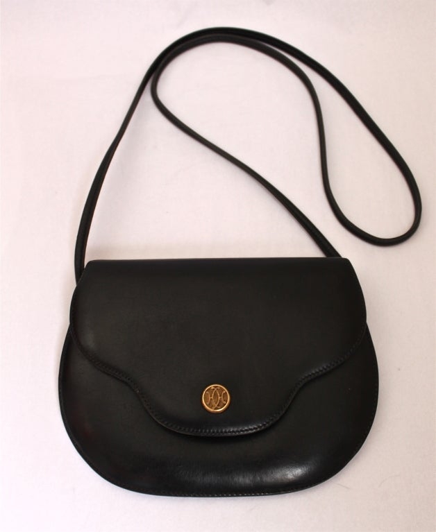 Petite black box leather small bag with decorative snap closure by Hermes dating to the 1970's. Bag is lined in goatskin and has one interior compartment with a strap that can be tucked in for use as a clutch. Bag measures 8