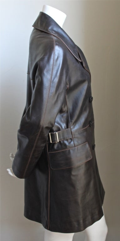 "Chocolate brown distressed double breasted leather jacket with silver side buckles and horn buttons from Azzedine Alaia. Coat is labeled a French size 40 which best fits a US 6. Coat measures approximately 37"" at bust, 15"" at smallest point of"