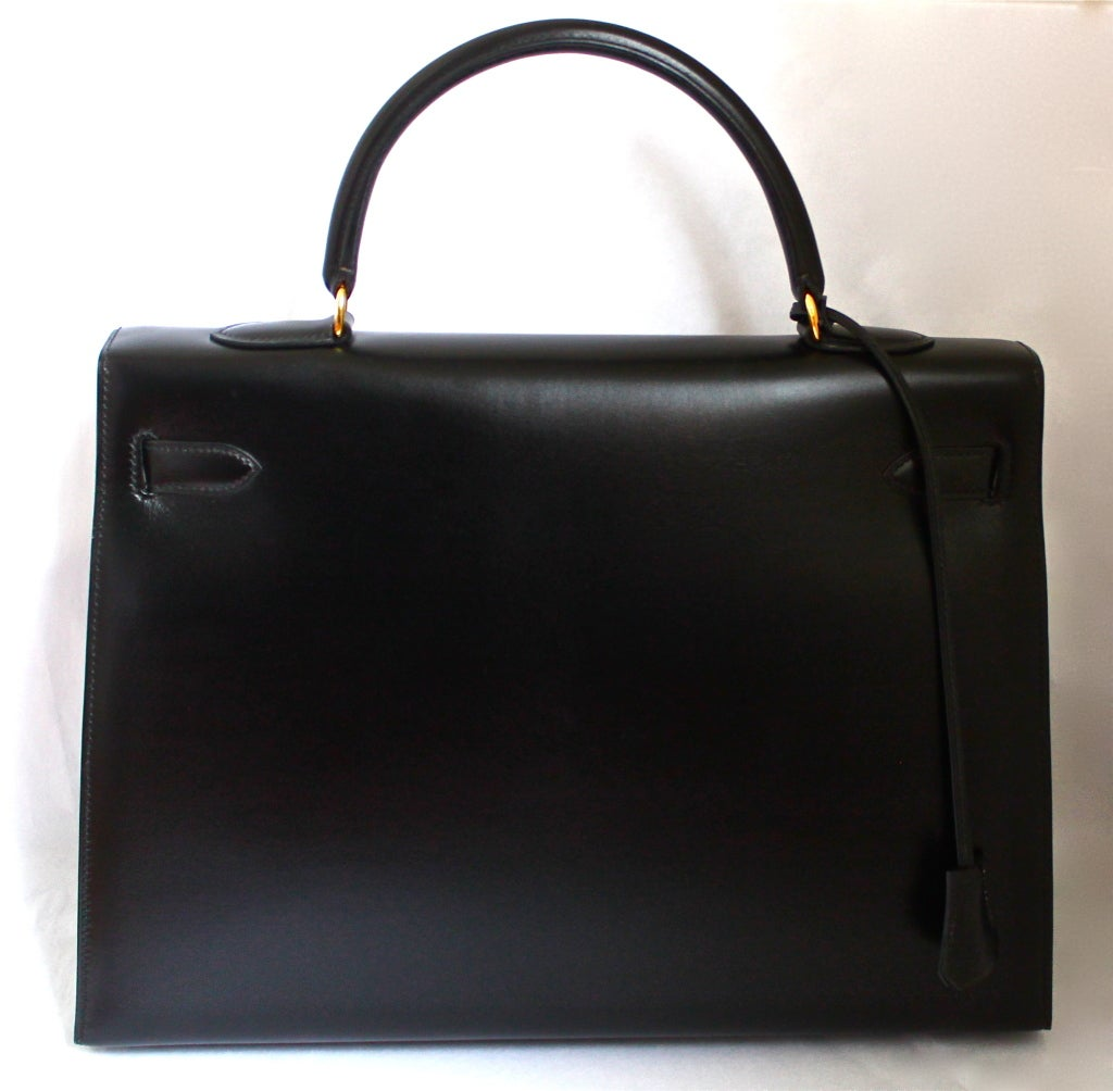 Classic jet black box leather 'Kelly' rigid model bag from Hermes dating to 1994. 35cm size. includes clochette, lock, keys, shoulder strap and original dust bag. Made in France. Excellent condition (looks very new ). More pictures are available