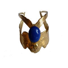 Gilt eagle cuff with blue glass cabachon