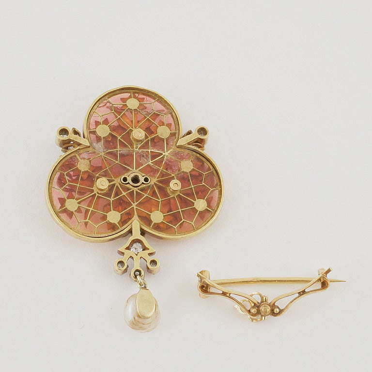 A French Art Nouveau 18 karat gold brooch with pearl and plique-a-jour enamel and diamonds. The brooch has a freshwater  pearl, and is of plique-a-jour enamel, and decorated with old mine cut and rose cut diamonds weighing approximately .25 carat.