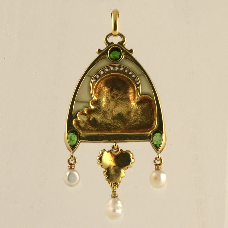 A French Art Nouveau 18 karat gold pendant with diamonds, pearls and peridots. The pendant features a plique-à-jour background with rose-cut diamonds with an approximate total weight of .60 carat, 3 freshwater pearls and 3 pear and round-cut