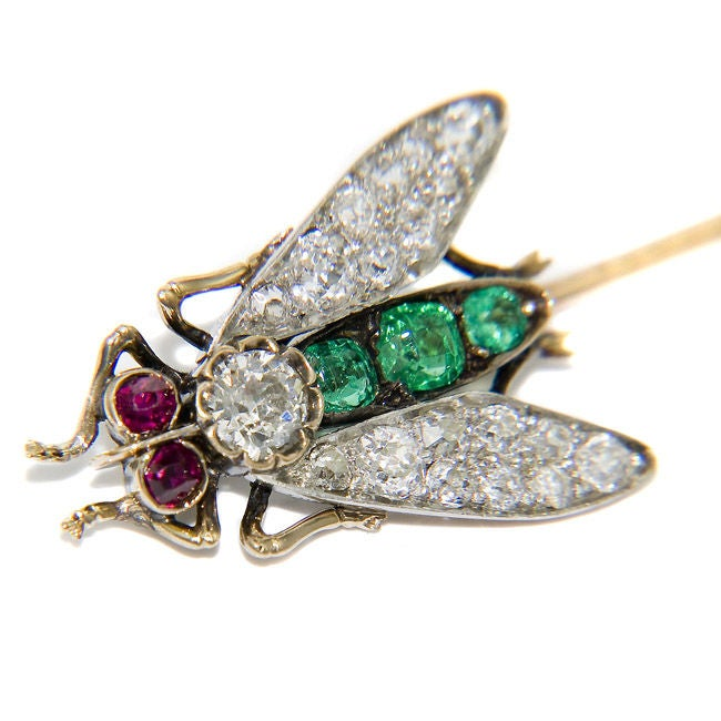 Platinum top, Gold back Fly Stickpin, set with Old mine cut Daimonds, Cushion cut Emeralds and Ruby Eyes. The Fly itself measures 7/8 Inch