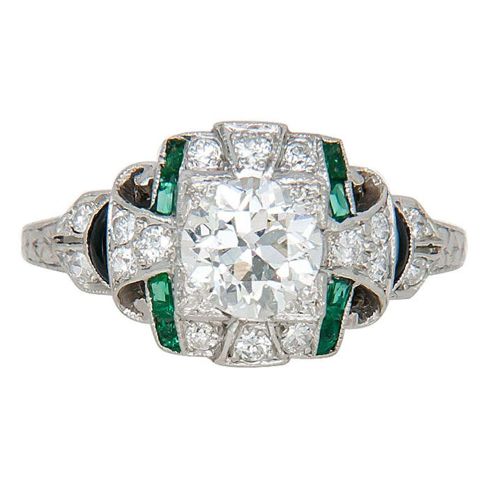 Circa: 1930s original Art Deco Platinum Engagement Ring, centrally set with an .88 Carat European cut Diamond, I Color and SI Clarity. The mounting is further set with smaller Diamonds, Emeralds and Onyx and has engraved Design work. Finger size = 5