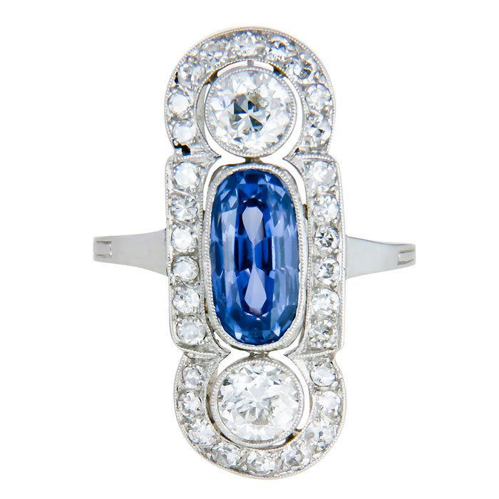 Wonderful Edwardian Platinum, Diamond and Sapphire Ring, set with an Oval-Cushion Ceylon Sapphire, approximately 1 carat. and further set with 2 old European cut Diamonds totaling .90 carat and surrounded by approximately 1 Carat of smaller old