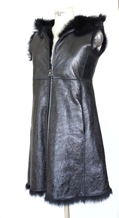 Guaranteed authentic Prada fabulous A line long sleeveless vest with hoodie. Jet black patent 'distressed' leather lined in jet black lush sheep fur. Full length front zipper with subtle stitch empire detail.  Sleeveless.  Fur edges hem and