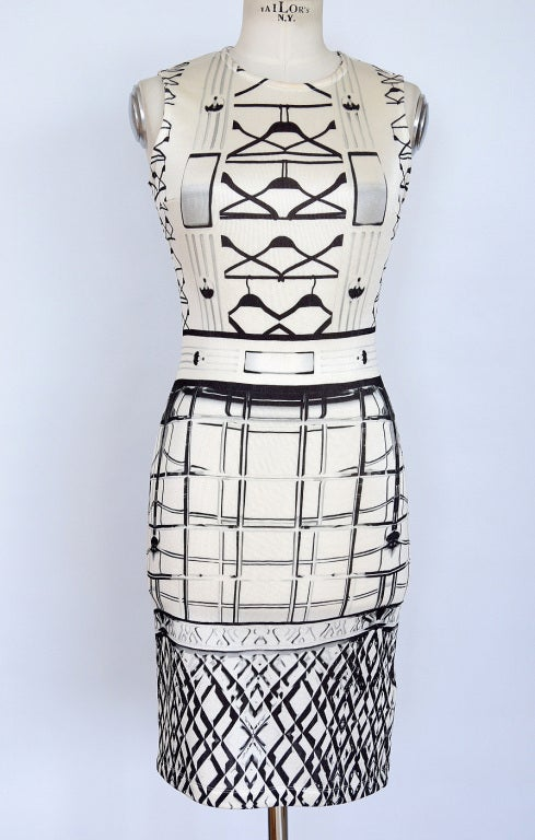 Guaranteed authentic MARY KATRANTZOU fabulous STARBRIGHT dress.   Cream colored sleeveless dress with a high round neck. Fun pattern of hangers and suspenders with a belt in black at top with abstract patterns at bottom. Fabric is viscose,
