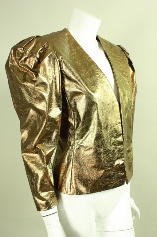 Vintage jacket from Bill Blass dates to the 1980's and is made of metallic gold leather.  It features massive leg-of-mutton sleeves that are gathered at the shoulders with shoulder pads to create additional fullness.  V-neck.  Center front hook and