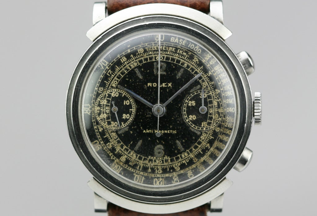 This is an early and rare Rolex hooded lug chronograph wristwatch, reference 2916, which almost never comes up for sale. This Rolex has an original black gilt dial with seconds and telemetre tracks, needle hands, two small black registers, oval pump