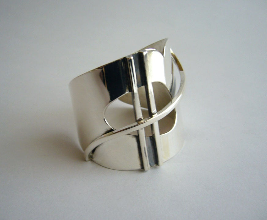 An early and rare sterling silver bracelet designed by Henry Steig of New York City.  Construction is made of sterling silver square bar and sheet stock with cut out design, giving the piece a lyrical theme.  Bracelet measures about 5 1/4