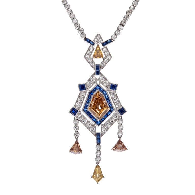 Striking and unusual art deco necklace with a brilliant array of natural colored diamonds, white diamonds and blue sapphires. The center of the drop pendant is a 3 carat kite shaped natural brown diamond. Additionally there are approximately 5.50