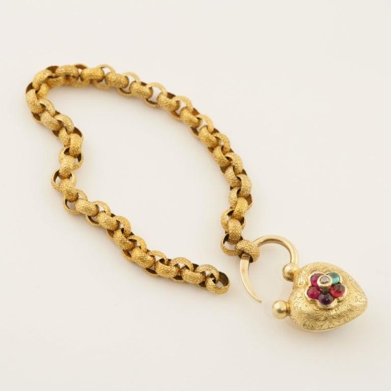 An English Antique bracelet with diamond, rubies, emerald, garnet and amethyst. The 15 karat bracelet has 1 rose-cut diamond, 2 cabochon rubies, 1 cabochon emerald, 1 cabochon garnet and 1 cabochon amethyst in a heart shaped 18 karat gold locket