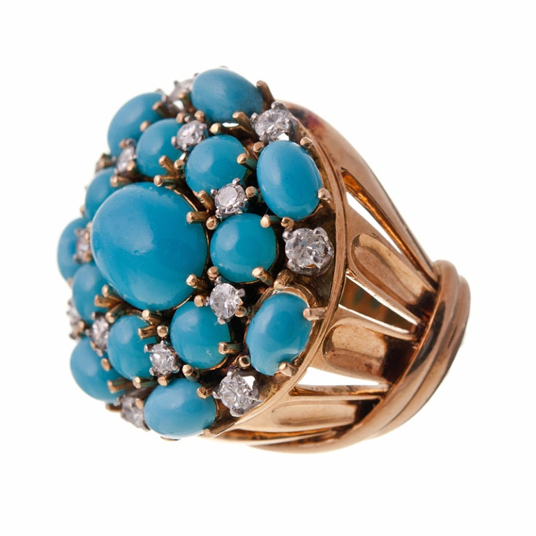 Fantastic 1950s classic cluster ring with bright turquoise cabochons set in 18k yellow gold. The turquoise is complimented by fifteen single cut diamonds peppered about to add some sparkle and an additional dimension to this playful design. The