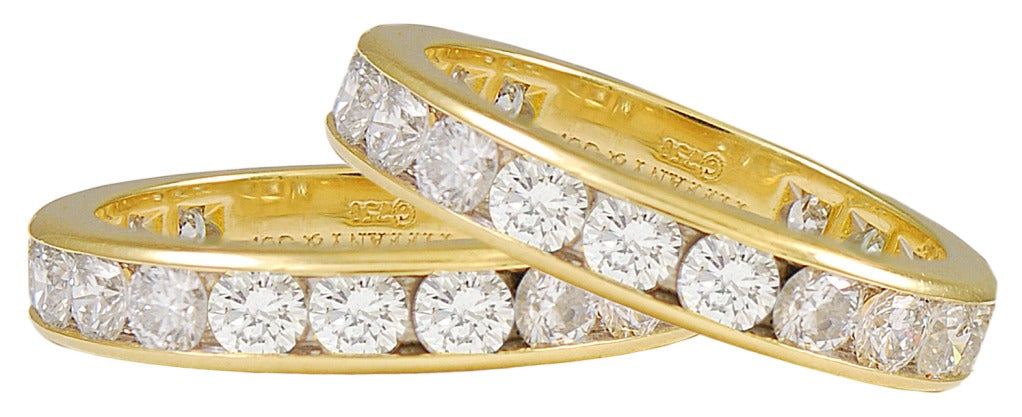 Outstanding pair of diamond eternity rings, made and signed by Tiffany & Co.  Large juicy brilliant stones totaling 6 cts., set in 18k yellow gold.  Size 6 1/2. These are exceptional in size and quality. They are three times larger than most