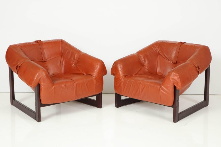 An all original pair of MP-091 loungers by Percival Lafer in Brazilian cherry and completely original caramel colored leather with original arm holding straps.