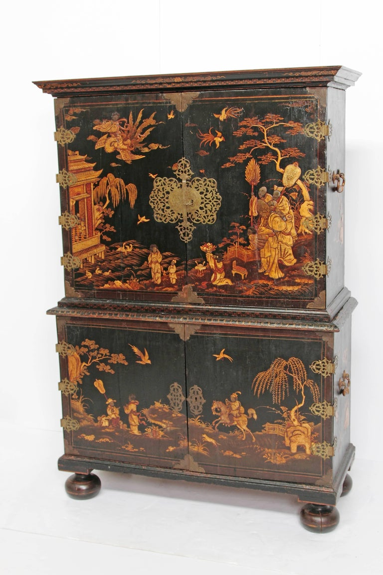 An English Queen Anne period collectors cabinet, black lacquer with raised gold decoration / Japanned (with chinoiserie decoration), two doors at top open to expose six (6) drawers, beside two (2) shelves, and a compartment with a door, base has two