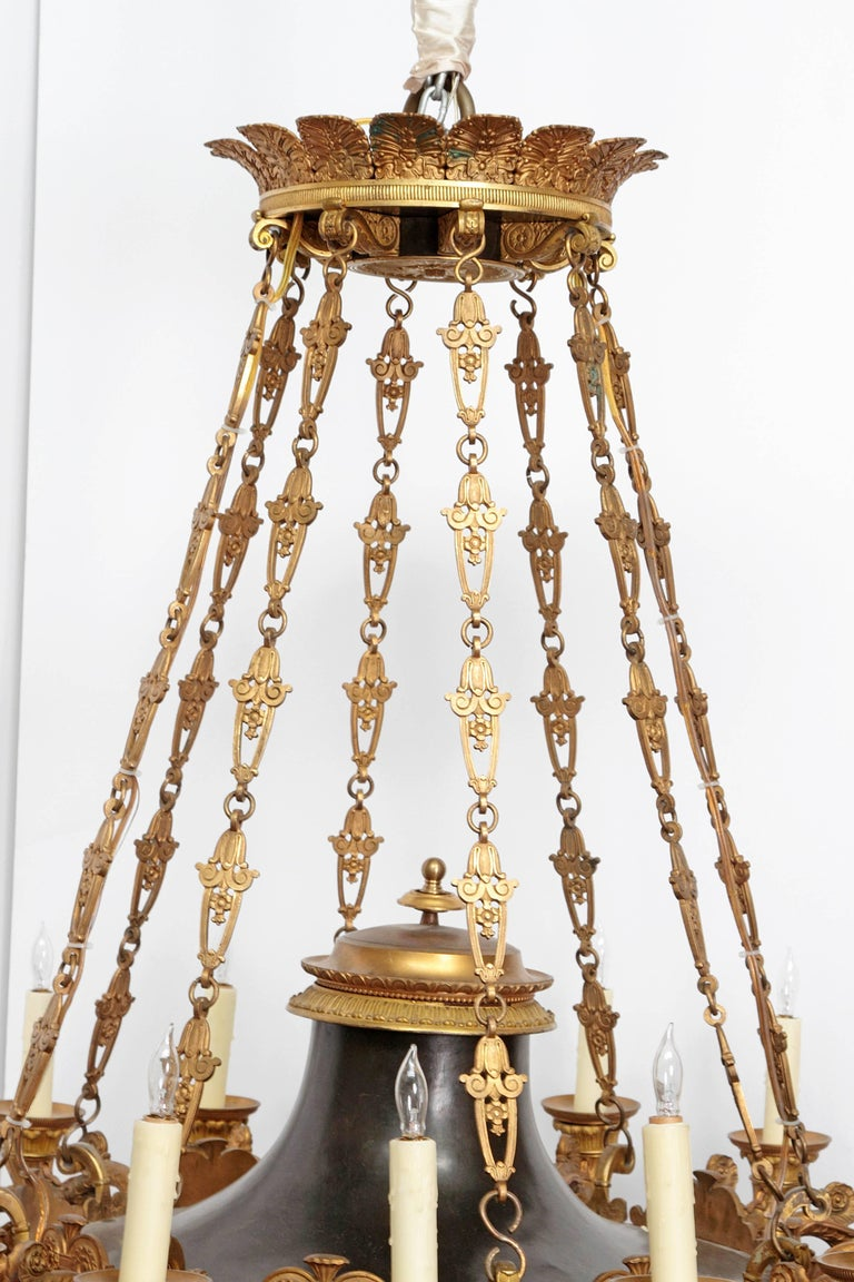 A large French Empire patinated and gilt bronze argon chandelier with 16 lights. Crown as top with palmette motif. Hanging chains supporting black disc forms with decorative trim holding lights. Centre pendant at bottom, early 19th century, France.