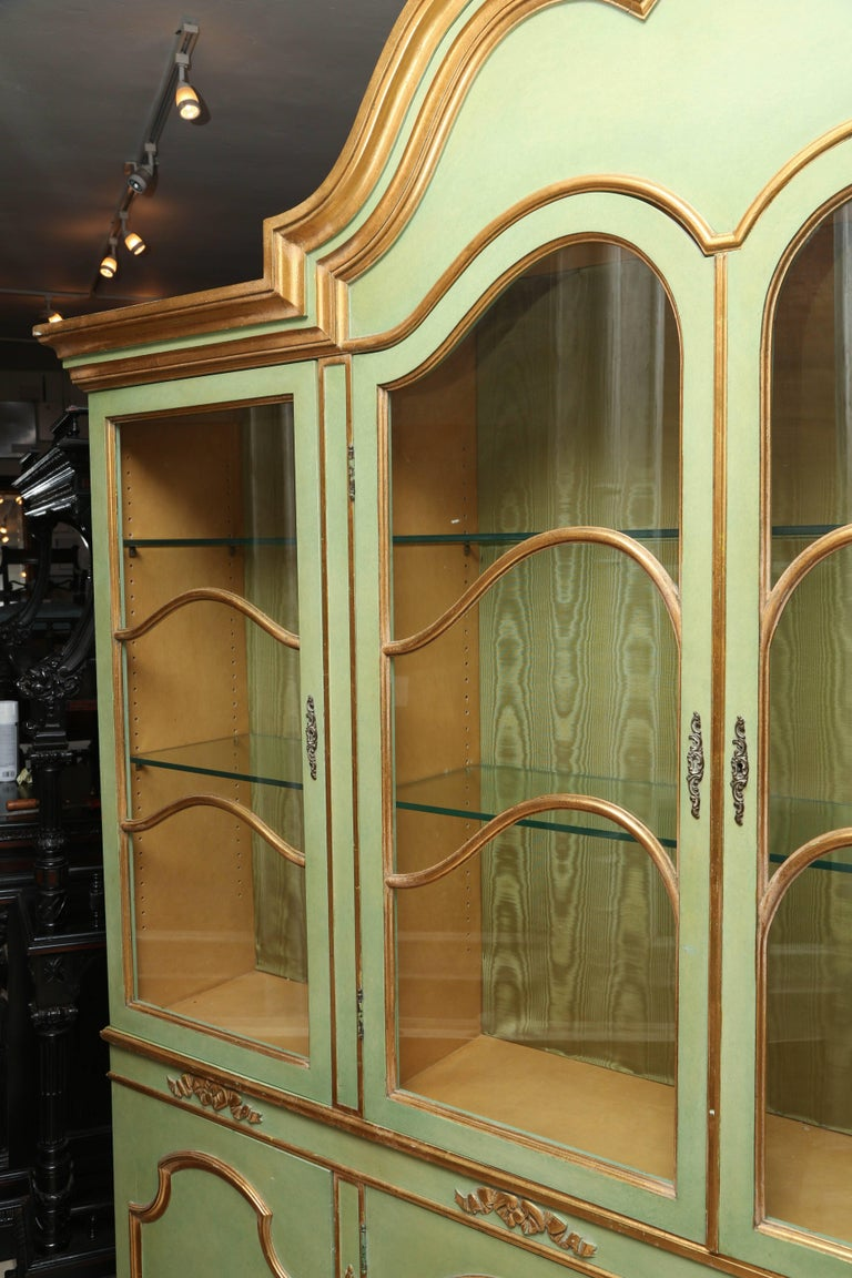 This is a superb very elegant antique style bookcase or cabinet in two parts with lighting inside . the upper section with a raised molded scroll cresting over two glazed arched doors, with gilt arched mullions, opening to shelves; the lower part