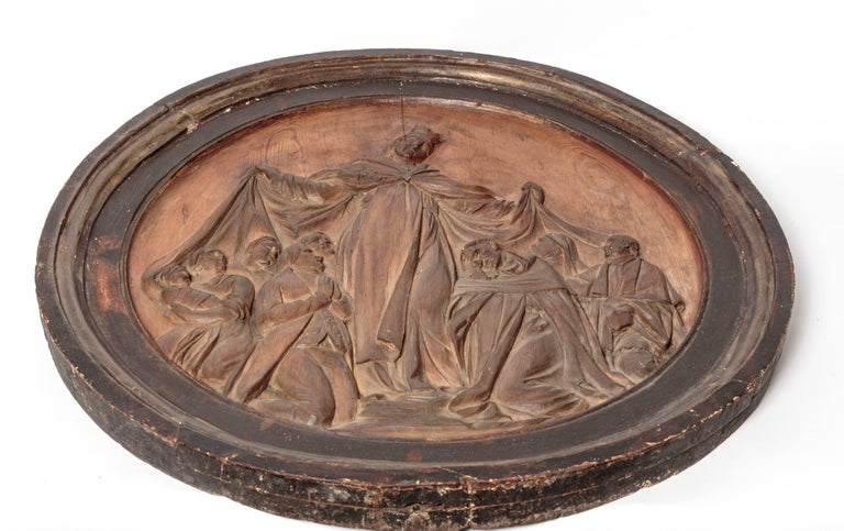 Beautiful hand-carved religious artifact depicting Virgin Mary surrounded by church and state figures. Base relief form finishing in round frame.