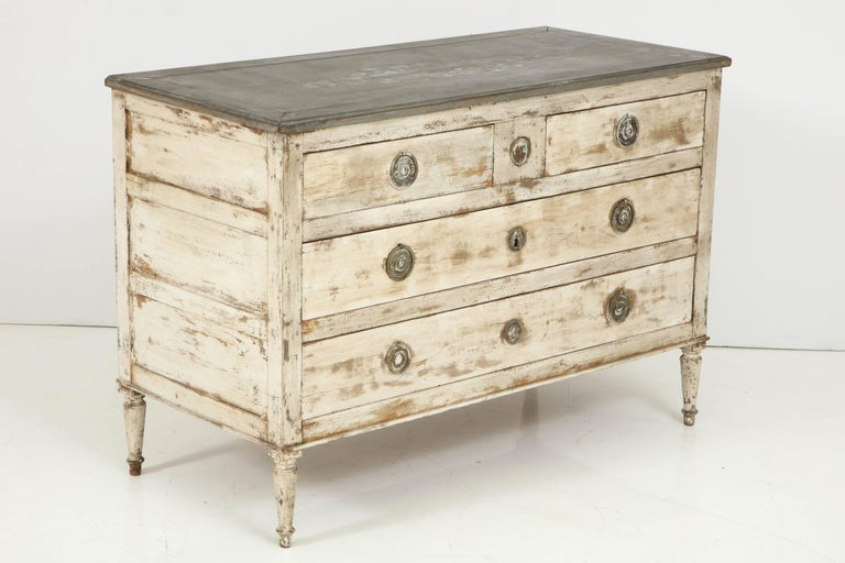 An early 19th century Directoire period chest with a lovely grayish white faded finish. The rectangular top is painted gray and surmounts two smaller top drawers and two larger lower drawers. The ring drawer pulls are in bronze and the chest is