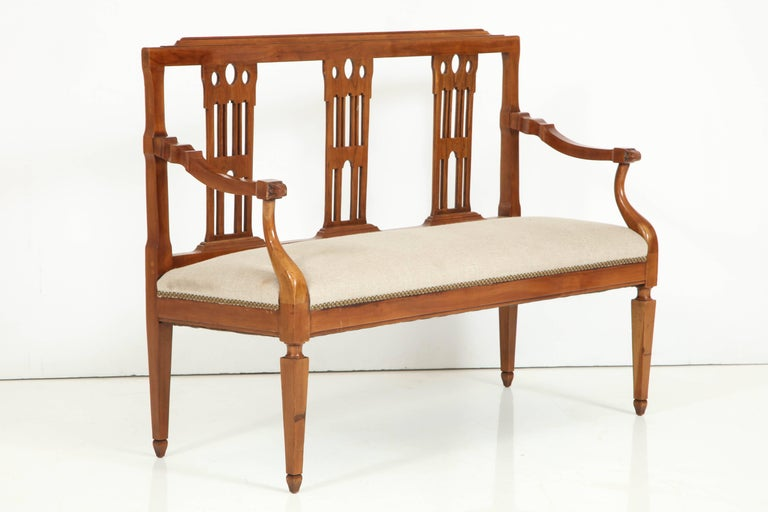 A beautifully made and well proportioned small fruitwood Italian bench, with an elegant, slatted back and curved arm supports and raised on squared, tapered legs. This neoclassical style bench is covered in a natural linen with nailhead trim at
