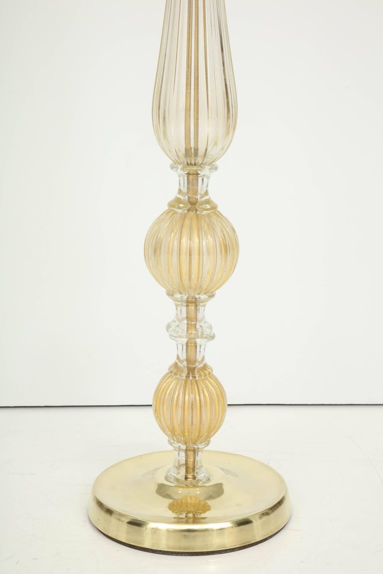 A magnificent floor lamp in Murano glass with gold leaf inclusions. The exquisite detail, including the fluted glass, the clear glass connectors and the brass base, give this lamp a sculptural quality. It not only provides light, but is a work of