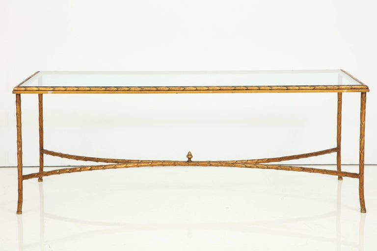 A gilt bronze cocktail table with a glass top attributed to Maison, Baguès, France. The glass top sits on the table frame with a leaf motif, characteristic of the elegance of Maison Baguès. The stretcher at base, composed of two curved elements, is