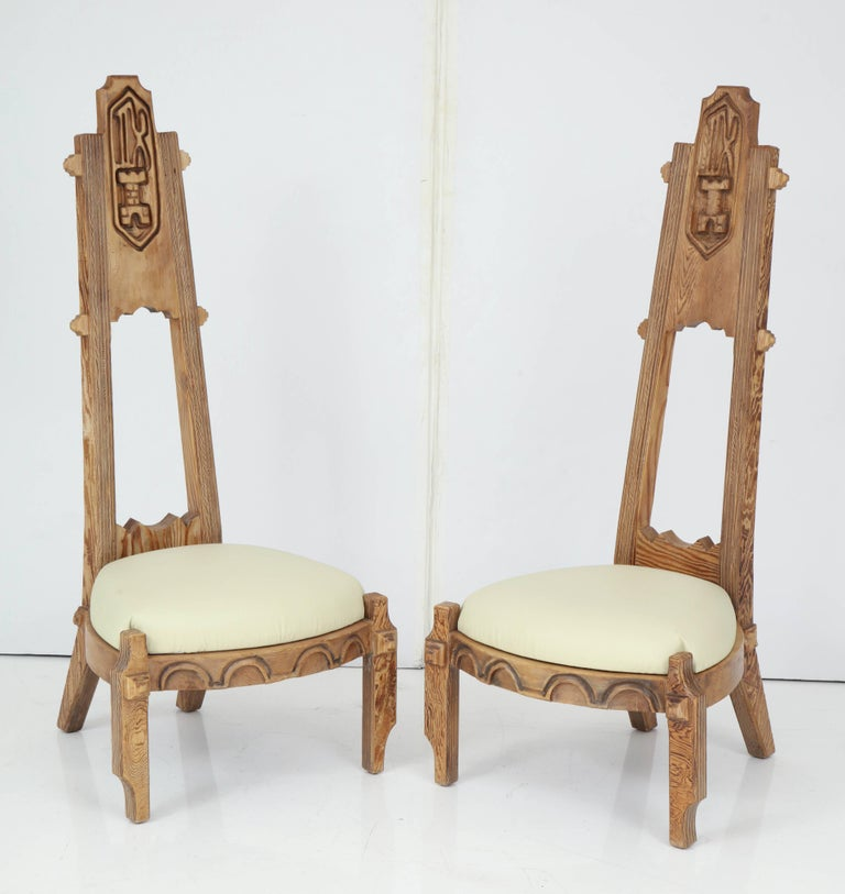 Pair of chairs with very tall backs having deep carved designs of Bishops from chess game with white leather seats.