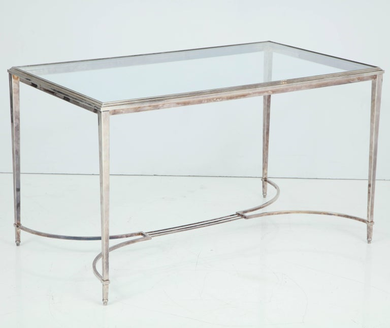 French silvered bronze vanity or writing desk with glass top, tapering square legs, and delicate stretcher base, circa 1940.