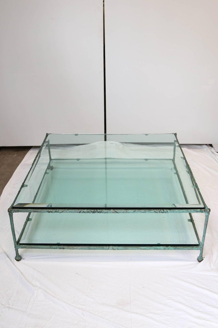 Two thick glass levels for this square midcentury coffee table in bronze in the style of Alberto Giacometti.